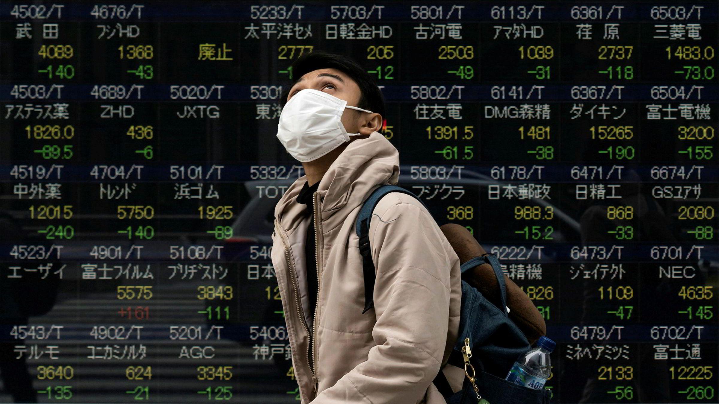 En fotgjenger går forbi Nikkei i Tokyo som falt mer enn 3,5 prosent da den åpnet mandag.