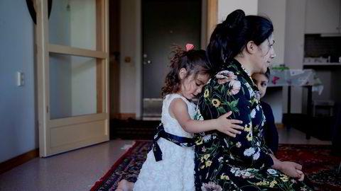 Homa Mohammadi sitter på gulvet i omsorgsboligen på Straume, litt utenfor Bergen. Datteren Maria holder rundt moren, som er utvist fra Norge. Ved siden av sitter sønnen Meriwan.