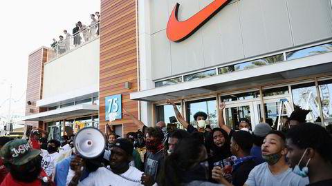 Fredelige demonstranter i Long Beach i California forsvarte en Nike-butikk mot plyndring i pinsehelgen.