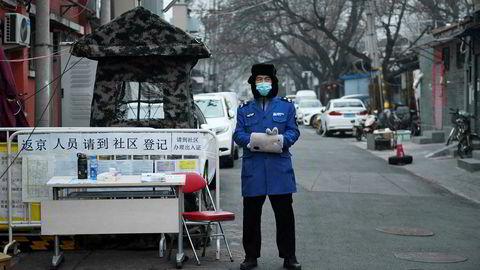En sikkerhetsvakt med ansiktsmaske for å beskytte seg mot Covid-19 koronaviruset ved et checkpoint i Beijing. Myndighetene mener nå å ha fått kontroll på epidemien.