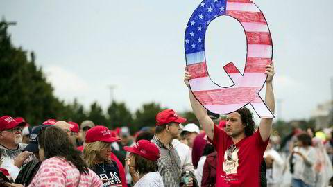 En demonstrant holder en stor Q mens han venter på å komme inn på et valgkampmøte med president Donald Trump i Pennsylvania i begynnelsen av august.