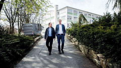 Daglig leder i K2 Bolig Sigve Hebnes (til venstre) og Øyvind Mikalsen i Camar Eiendom på tomten de har kjøpt i Stavanger sentrum. Den store lagerhallen i bakgrunnen er vernet og skal beholdes.
