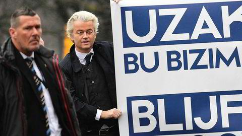 PVV-lederen Geert Wilders (t.h.) holder her opp et banner i protest mot Tyrkia utenfor den tyrkiske ambassaden i Haag tidligere denne måneden. Mens Wilders protesterte satte den sittende statsministeren Mark Rutte fra sentrumspartiet VDD hardt mot hardt i konflikten med Tyrkia, som kan ha ført til økt oppslutning for VDD.