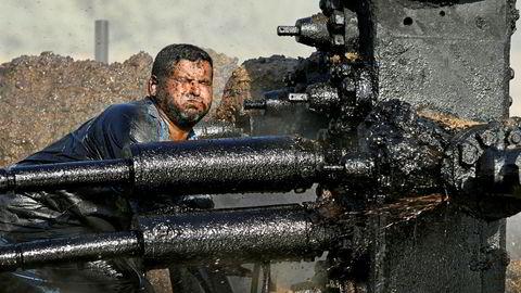 En Irakisk oljearbeider prøver å reparere en pumpe på en oljebrønn i Bod Al-Sham, Irak. Spenningen er stor foran ukens møte mellom de 24 landene som har inngått avtalen om kutt i oljeproduksjonen.