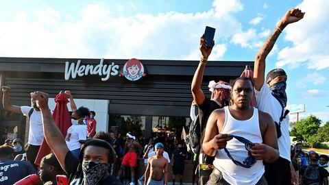 Demonstranter samlet seg utenfor hurtigmatrestauranten lørdag. Senere på kvelden ble den satt i fyr i protest mot politiet.