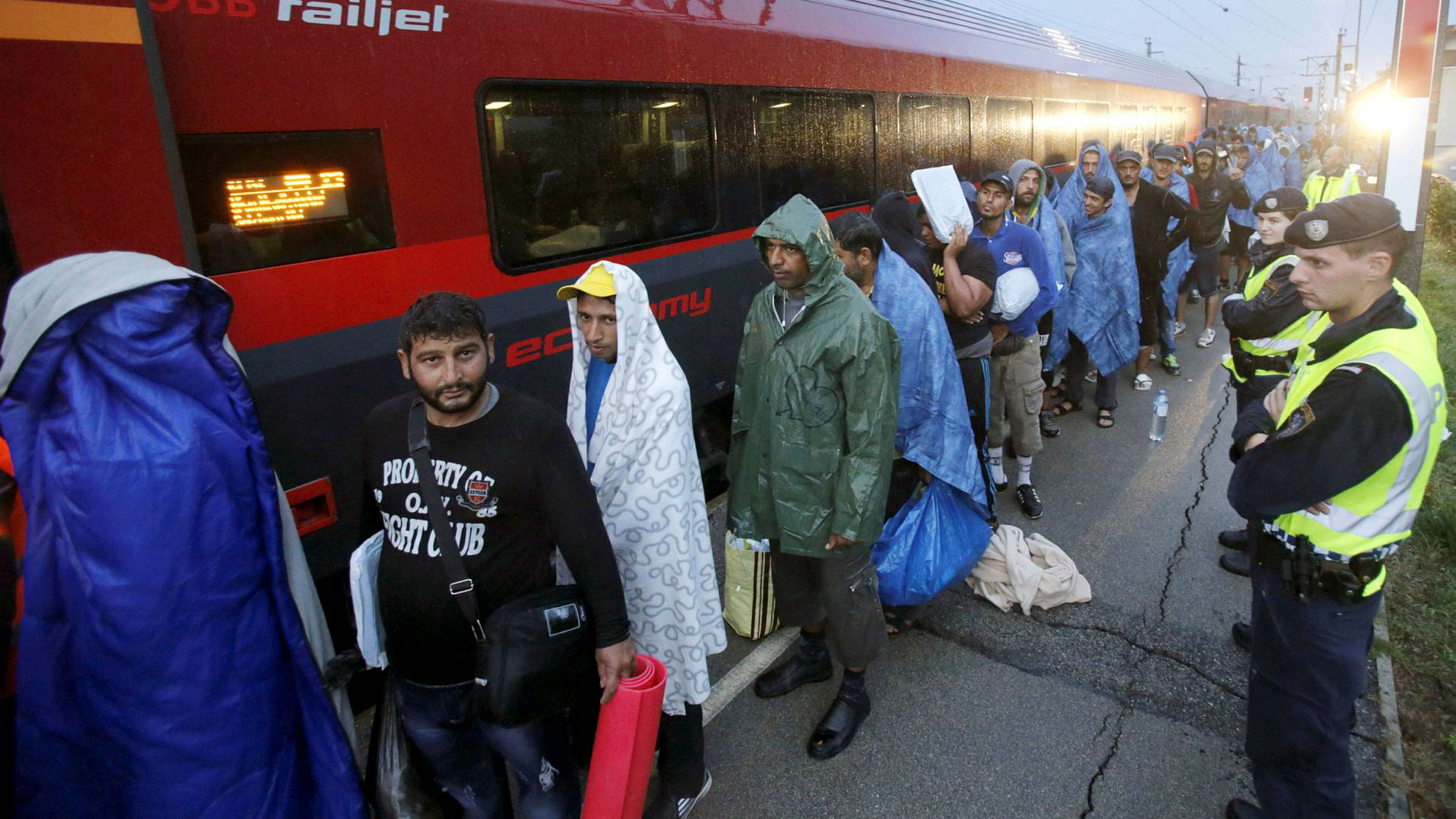 Migrants arrive at the Austrian train station of Nickelsdorf to board trains to Germany, September 5, 2015. REUTERS/Heinz-Peter Bader/File Photo ---