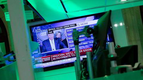 Donald Trumps pressekonferanse overværes på en skjerm på New York Stock Exchange, som holder til på Wall Street. Presidentens løfter om krisetiltak bidro til at indeksene steg tirsdag.