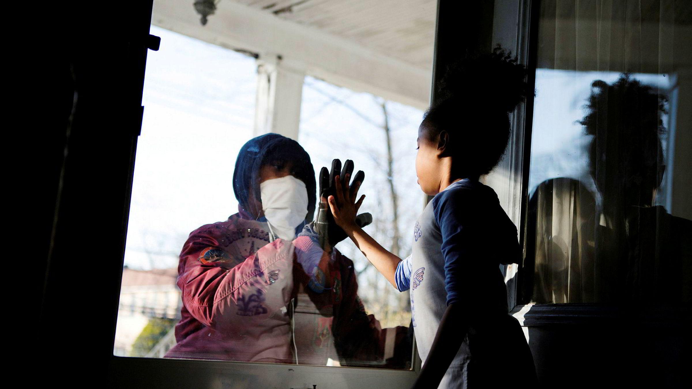 Sosial distanse preger verden under epidemien. Her hilser en helsearbeider på datteren sin gjennom en glassdør.