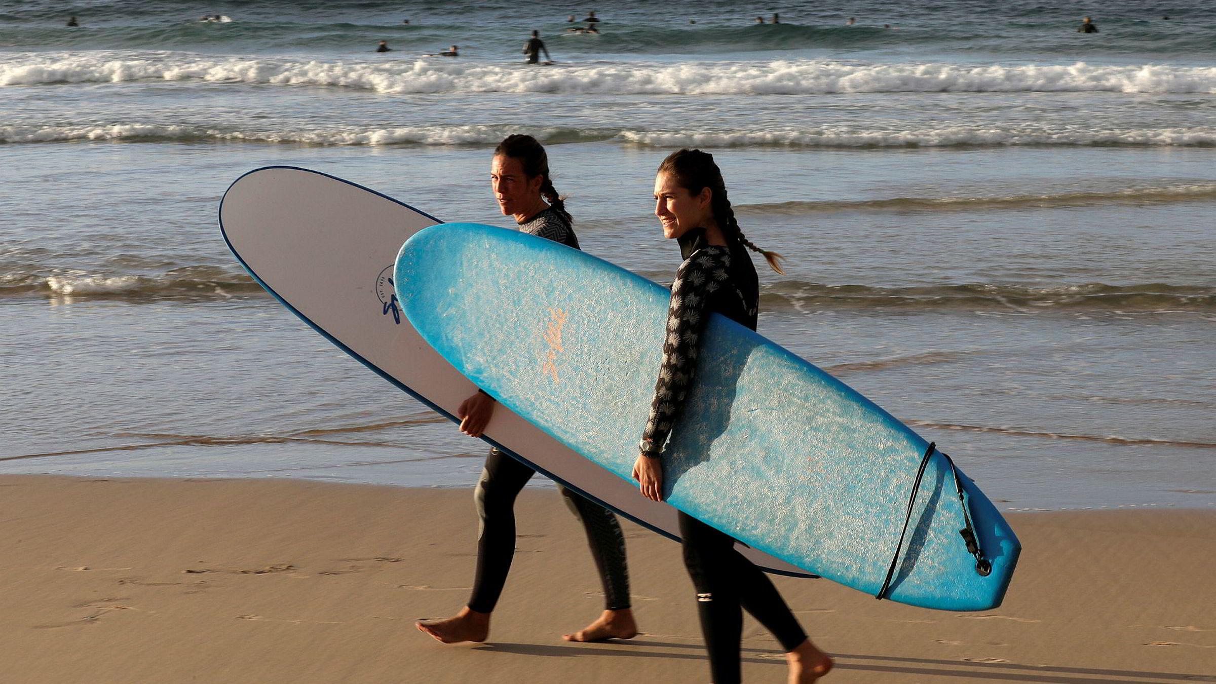 Surfere på vei ut i vannet på Bondi Beach i Sydney. Stranda har til nå kun vært åpen for at surfere og svømmere kan trene, men fredag åpnes strendene for hele befolkningen i New South Wales.