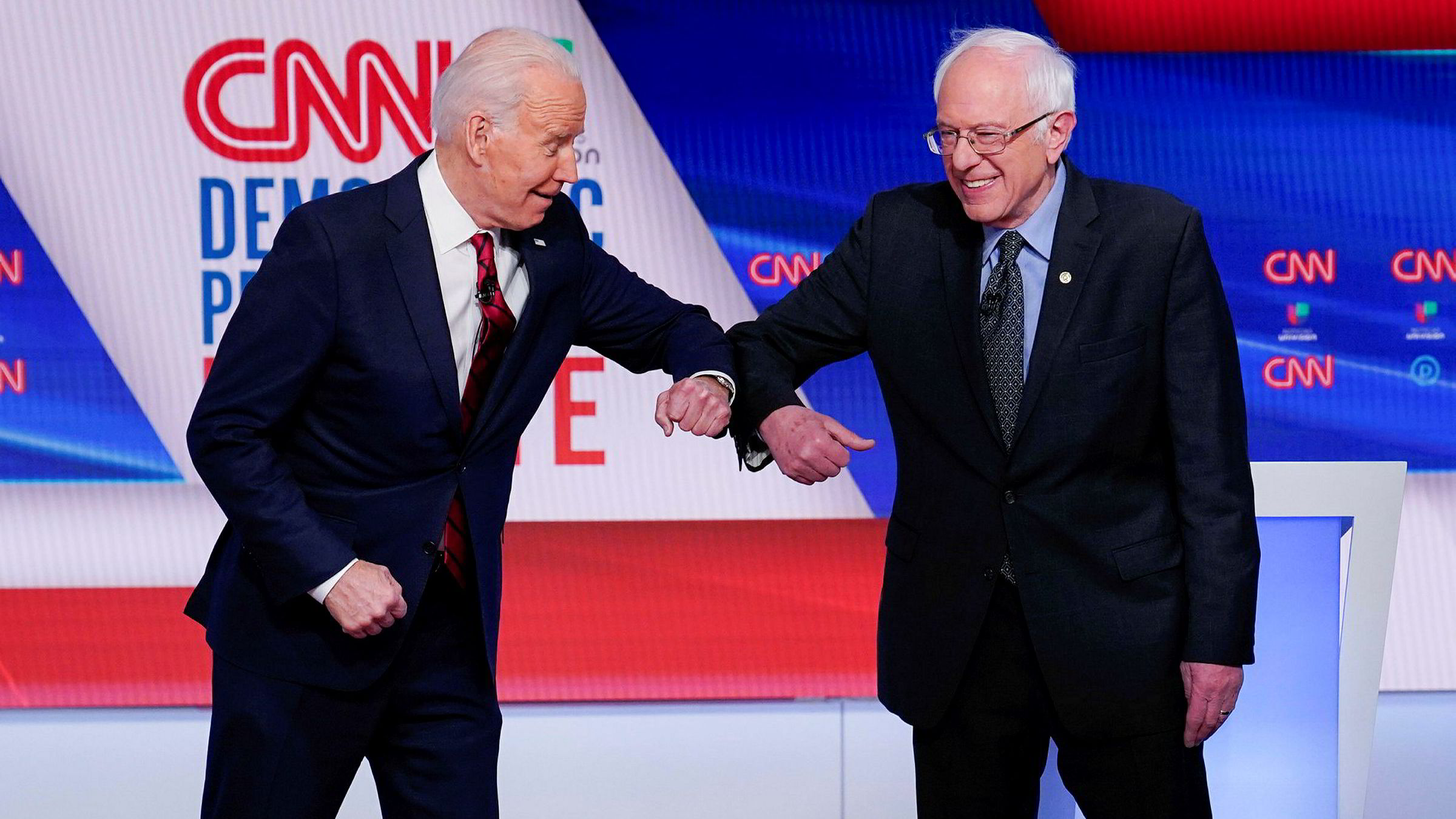Tidligere visepresident Joe Biden (til venstre) gjør «korona-hilsen» med Bernie Sanders. Biden ligger godt an til å bli Demokratenes presidentkandidat, men også per i dag til å bli USAs neste president.