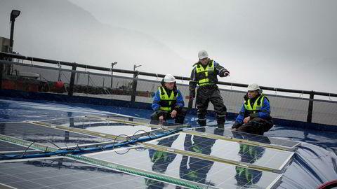 Ocean Sun-gründerne Øyvind Christian Rohn (sittende) og Børge Bjørneklett (til høyre) viser frem solcellepanelene for Bjørn Thorud (til venstre) i Multiconsult. I bakgrunnen snakker Arnt Emil Ingulstad (til venstre) fra Ocean Sun med Stanislas Merlet fra Multiconsult.