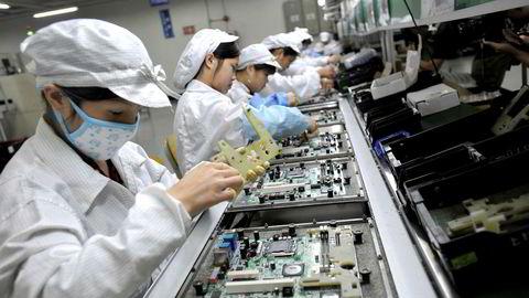 Robotene er i sving også utenfor Vesten. Foxconn, et taiwansk selskap som setter sammen rundt 40 prosent av verdens elektronikkprodukter inkludert Apples Iphone, sparket i fjor 60.000 ansatte, ifølge BBC. Her kinesiske arbeidere ved Foxconns fabrikk i Kina.