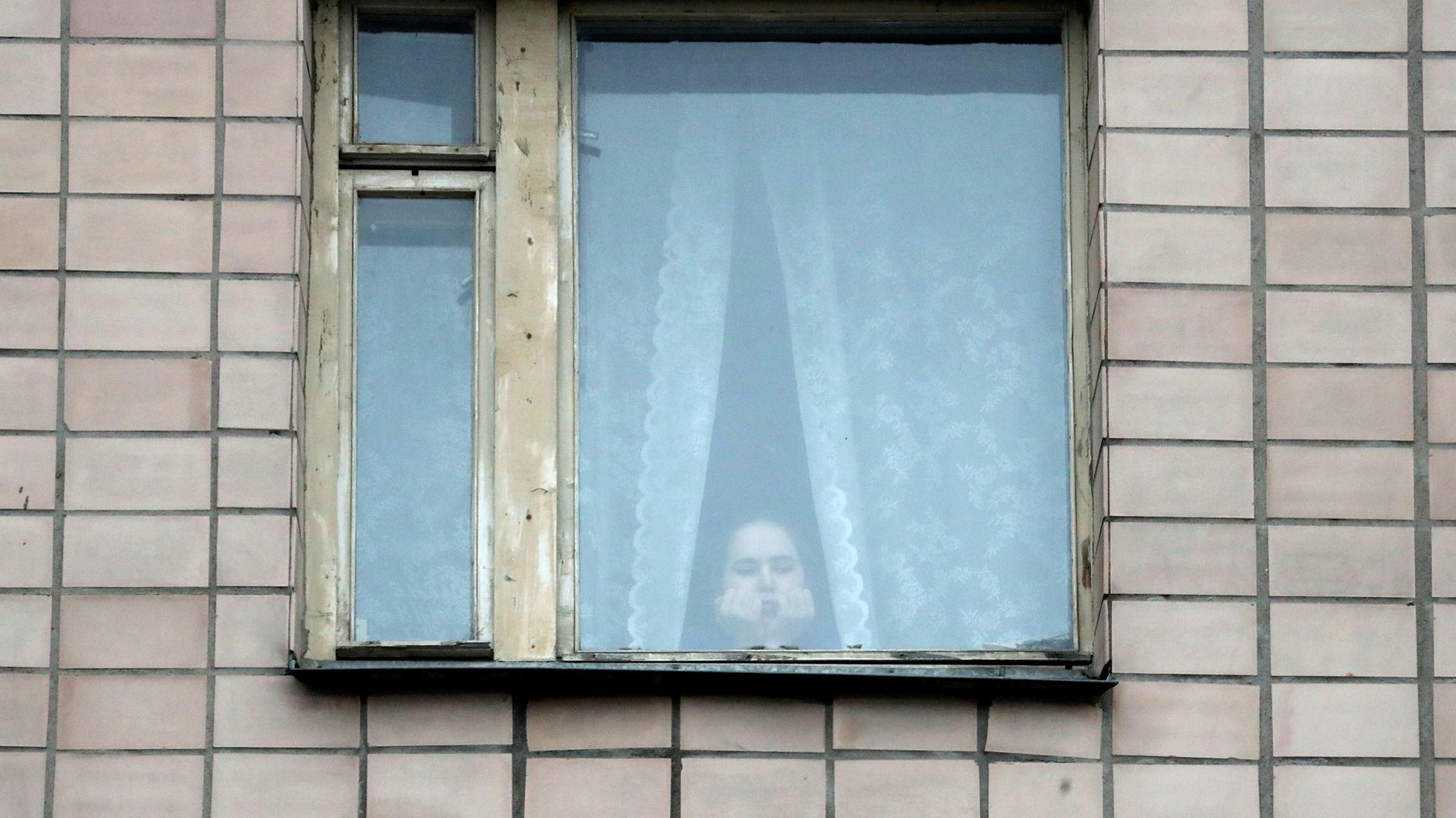 En ung kvinne sitter i korona-karantene i St. Petersburg. De kan blir mange de nærmeste ukene.