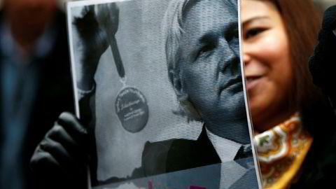En Julian Assange-tilhenger holder opp en plakat av ham i Ecuador mandag.