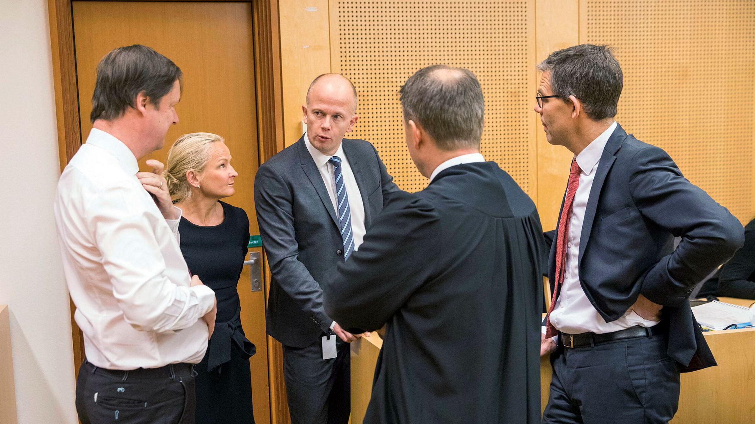 Forsvarerne John Christian Elden (fra venstre), Sol Elden, Svein Holden, Jan Erik Teigum (med ryggen til), og Vegard Aaløkken snakker sammen i Oslo tingrett under rettssaken om misbruk av au pair-ordningen.