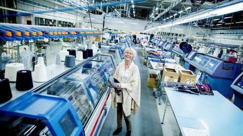 Dale-eier Hilde Midthjell i fabrikkhallen i Dalekvam mellom Voss og Bergen, ved siden av maskinen som syr Christiania-jakker på løpende bånd.