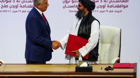 Mulla Abdul Ghani Baradar (til høyre), lederen for Taliban-delegasjonen, og USAs spesialutsending Zalmay Khalilzad, gir hverandre hånden etter signering av fredsavtalen lørdag.