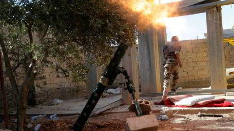 Et medlem av den USA-støttede opprørsalliansen SDF avfyrer en bombekaster i Raqqa i juli i år. Foto: AP/NTB scanpix