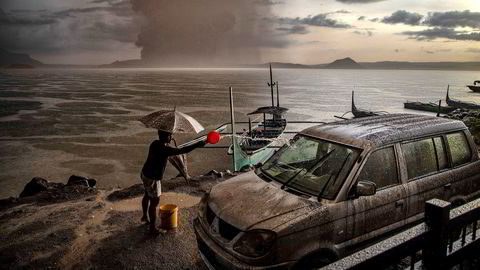 En mann vasker bilen for aske og regnvann etter utbruddet i Taal-vulkanen på Filippinene. Vulkanen ligger på en øy i en innsjø 66 kilometer sør for hovedstaden Manila, og søndag sendte den damp og aske en kilometer opp i luften.