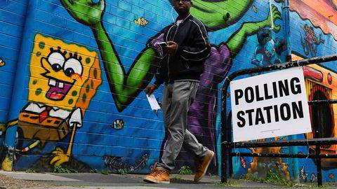 En mann går forbi et avstemmingslokale i Storbritannia.