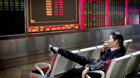 Et stort antall kvinner har skapt egne formuer – uten støtte fra arv eller skilsmisseoppgjør. Bildet viser en investor som følger med på en børstavle i Beijing.