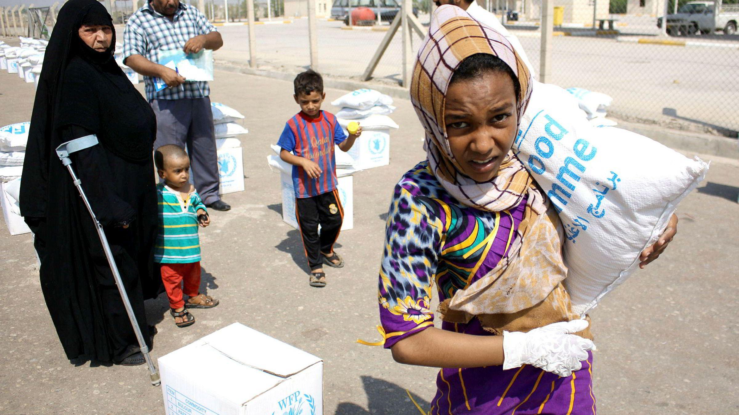 Det aller viktigste er å spille på lag med mottagerlandets myndigheter så lenge vi ser det slik at disse søker å fremme utvikling og velferd for brede lag av befolkningen. Her har en irakisk flyktningjente mottatt en sekk mat frai Basra i sør-Irak.