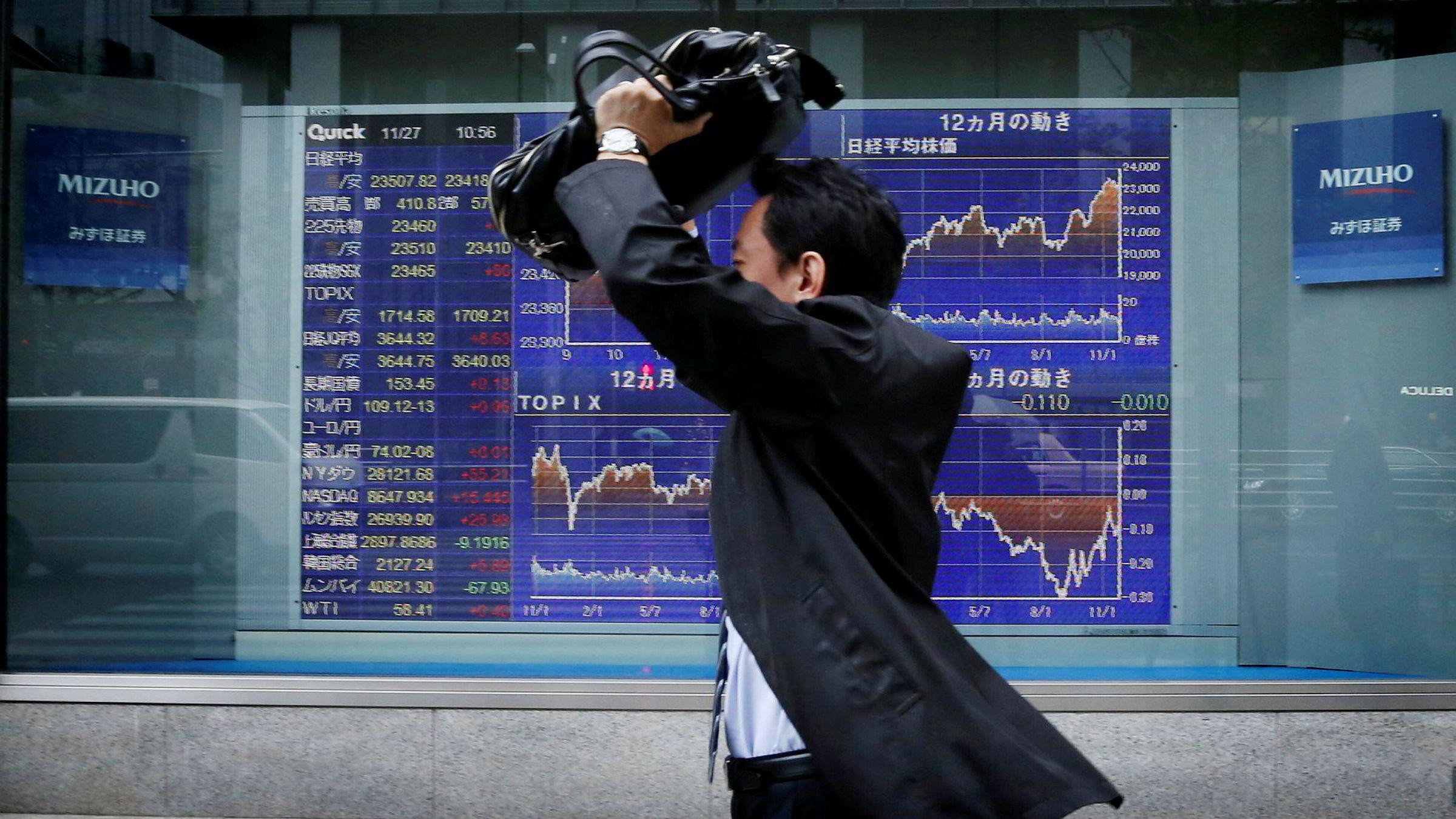 Tokyo-børsen har hatt en solid høst med en bred oppgang. Nikkei-indeksen nærmer seg nivåer den sist hadde på begynnelsen av 1990-tallet. Denne mannen passerte en kursoversikt i Tokyo sentrum onsdag morgen.