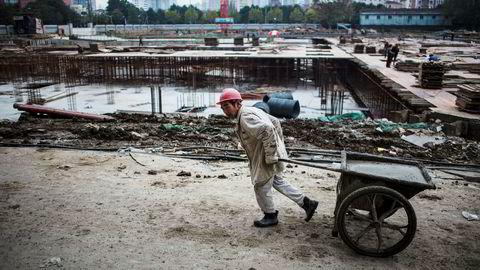 Råvarespekulanter har sendt prisene på jernmalm og stål kraftig opp i Kina. Nå strammer myndighetene inn i håp om å unngå nye bobler. Her fra en av Shanghais mange byggeplasser.