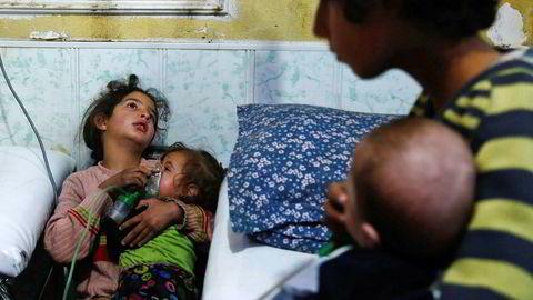 En ung syrisk jente holder en oksygenmaske over ansiktet til et lite barn etter lørdagens angivelige gassangrep.
