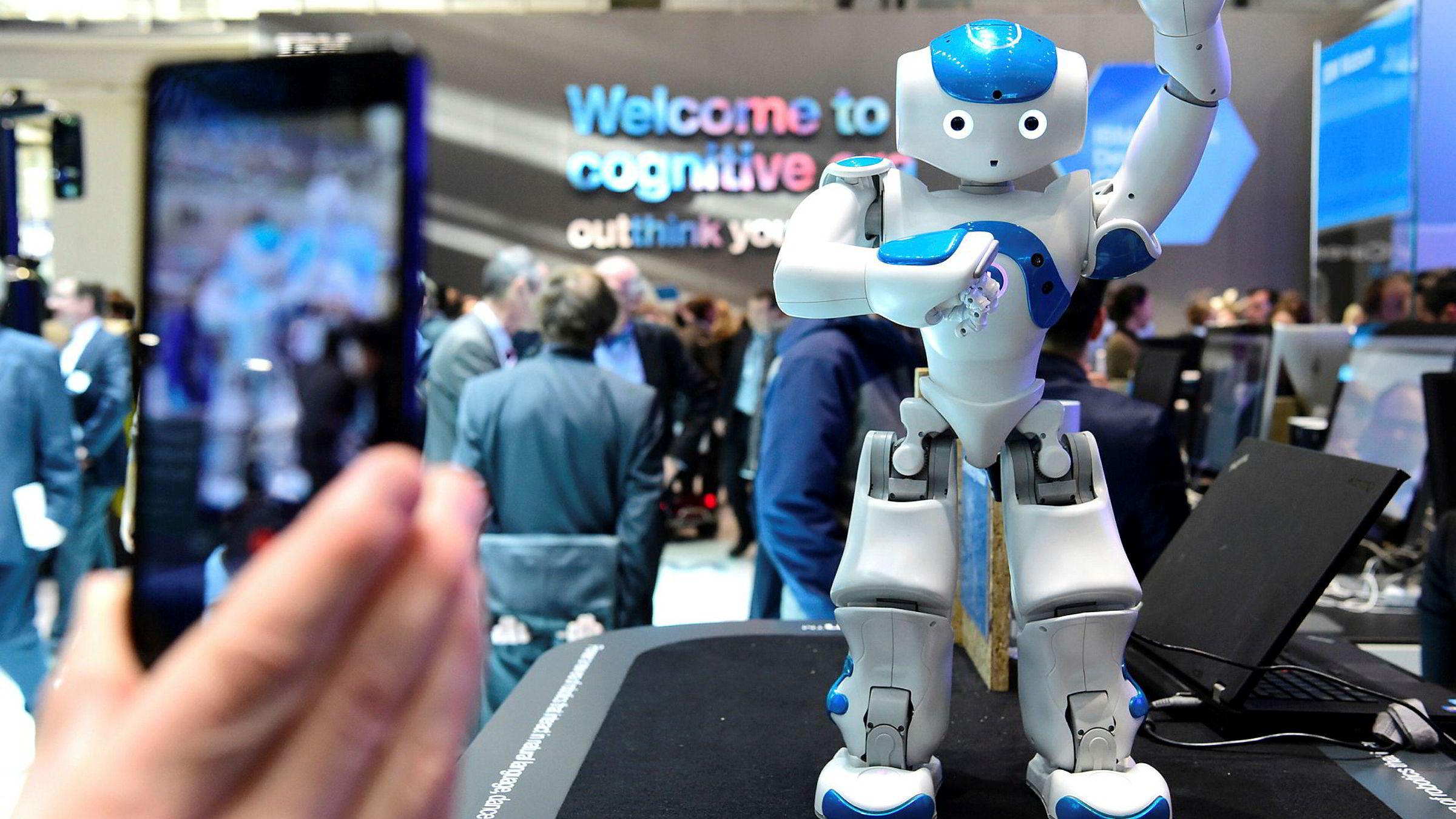 EU vil ha strengere regulering av roboter og kunstig intelligens (AI). På bildet tar en person bilde av en liten dansende robot på CEBIT-messen i Hannover i Tyskland i mars.