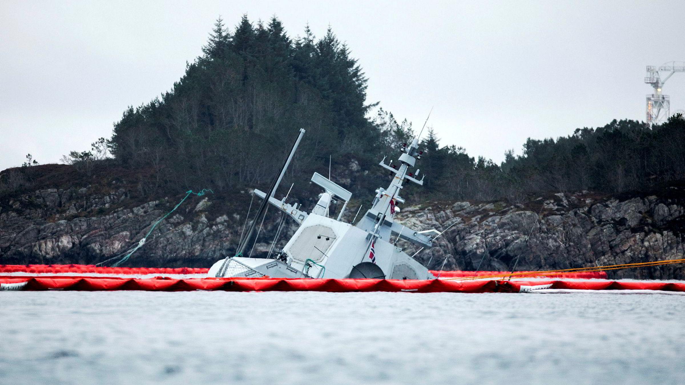 Fregatten KNM «Helge Ingstad» etter kollisjonen ifjor høst i Øygarden utenfor Bergen.  Det er trukket gule tau ut til akterenden av havaristen som så vidt stikker opp av vannet.