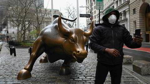 En mann med munnbunn tar en selfie foran den kjente oksen nær New Stock Exchange tidligere i mars.