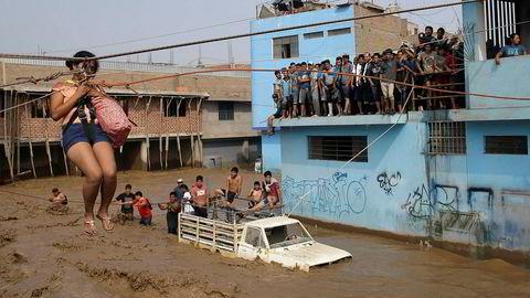 En kvinne blir heist i sikkerhet over en gate som er forvandlet til en elv i Lima i Peru.