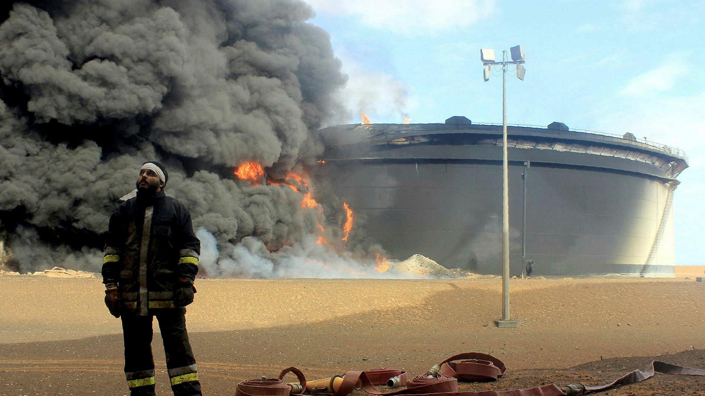 En libysk brannmann foran en oljelagerfasilitet i brann fra den oljerike Ras Lanuf-regionen i fjor. Det er dette området ulike militsgrupper nå kjemper over i Libya.