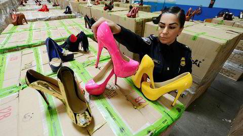 Høye grenseavgifter krever langt flere tollere. Her har en toller ved havnen i Long Beach i California beslaglagt falske Christian Louboutin-sko fra Kina.
