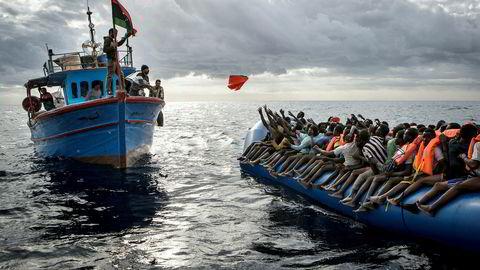Bildet viser libyske fiskere idet de kaster redningsvester til flyktninger som ønsker å krysse Middelhavet i håp om et bedre liv i Europa.