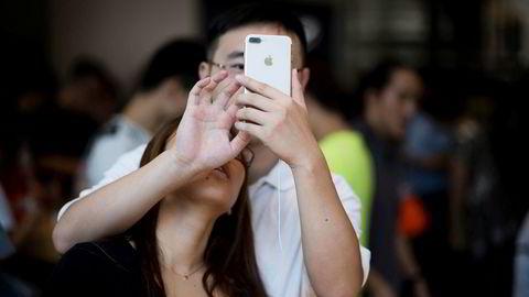 Apple er et av flere amerikanske selskaper som kan risikere tilbakeslag i Kina hvis Donald Trump innfører straffetoll mot landet. Her prøver et et kinesisk par Apples Iphone 7 i Shanghai i september.