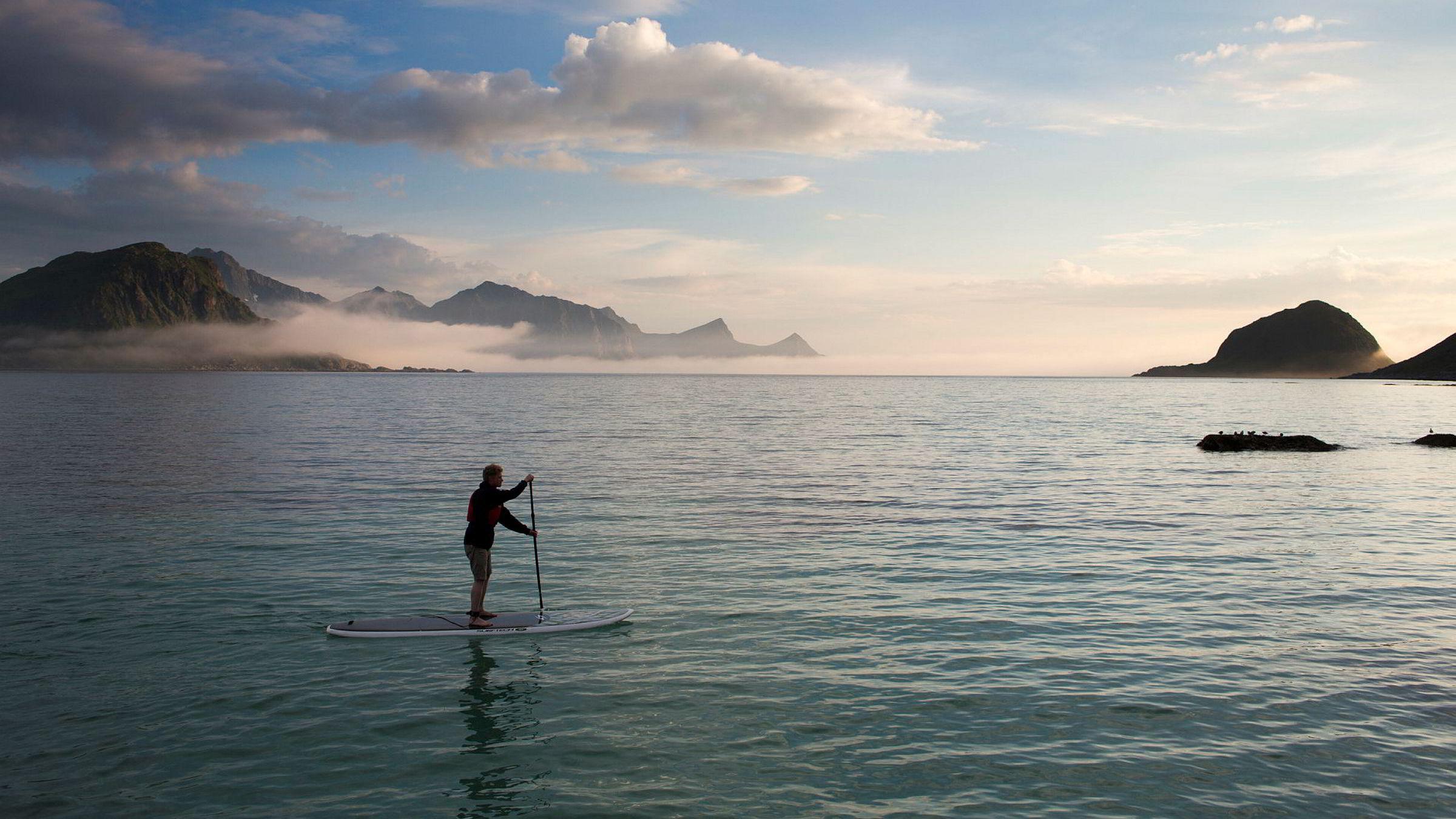 Ole Kristian Fjelltun-Larsen er en av stadig flere som leier ut SUP-brett til turister. Her padler han selv en tur ved Haukland i Lofoten.
