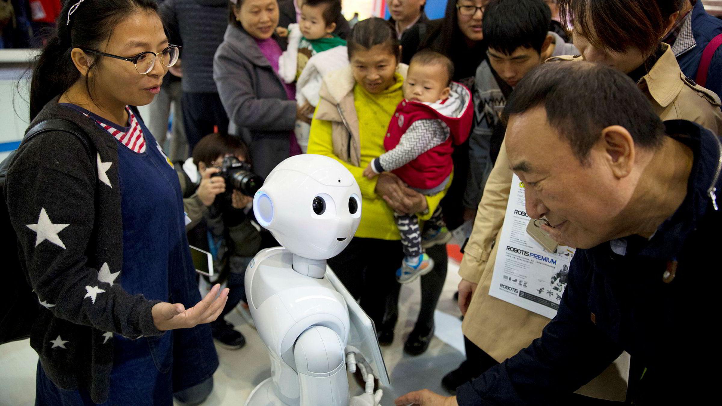 Utfordringen, både ved globalisering og robotisering, er hvordan man kan få den frigjorte arbeidskraften over i annet produktivt arbeid. Her hilser besøkendepå World Robot Conference i Beijing på roboten Pepper.