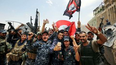 Medlemmer av Iraks føderale politi feirer med landets flagg i gamlebyen i Mosul etter seieren mot IS i helgen.