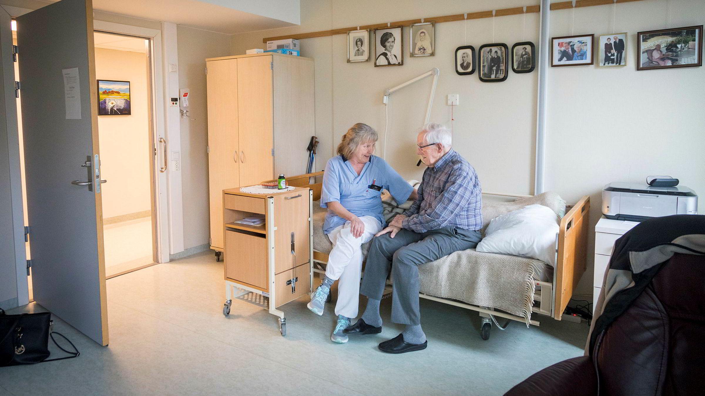 Hjelpepleier og tillitsvalgt Kitt Martinussen Bakari snakker med beboer John Fosse (98) på Sagenehjemmet. Bakari insisterte selv på å jobbe etter en større ryggoperasjon i fjor.