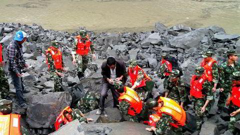 Kinesisk militærpoliti og redninsarbeidere i arbeid etter raset i Xinmo- landsbyen i Sichuan-provinsen.