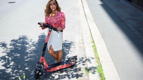 Christina Moe Gjerde er landssjef for Voi i Norge og Finland og er her avbildet i Oslo sentrum med en Voi-sparkesykkel av nyere type.