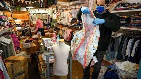 Gianfranco Mandas sorterer barneklær i butikken han fikk åpne igjen i Roma tirsdag.