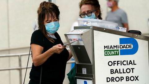 Valgmedarbeidere legger postsendte stemmesedler inn en mottakskasse i Miami. Med en knapp uke igjen til valget har flere titall millioner amerikanere til gode å returnere de ferdig utfylte stemmesedlene sine