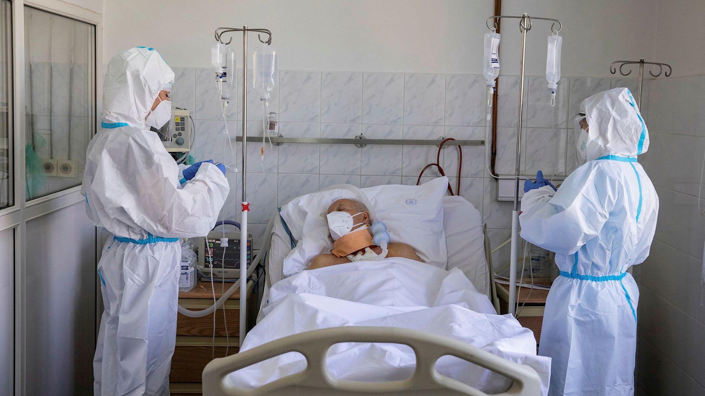 Helsearbeidere behandler en pasient for med koronavirus på en klinikk i Beograd, Serbia.