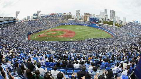 Det var nesten fulle tribuner da på Yokohama Stadium i Japan på søndag. Nye registrerte koronasmittetilfeller er mer enn halvert  i Asia på to måneder. I USA og Europa er det en dobling.