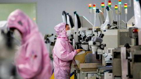Kinesiske fabrikker forsøker å komme i gang med produksjonen. Det kan bli store forsinkelser i produksjonen. Ansatte er redde for å reise på jobb. Her fra en databrikkefabrikk i Jiangsu-provinsen, hvor arbeidere forsøker å unngå smitte.