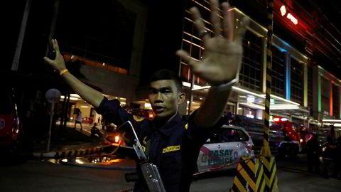 En sikkerhetsvakt stopper fotografer fra å gå inn i Resorts World Manila etter torsdagens angrep.