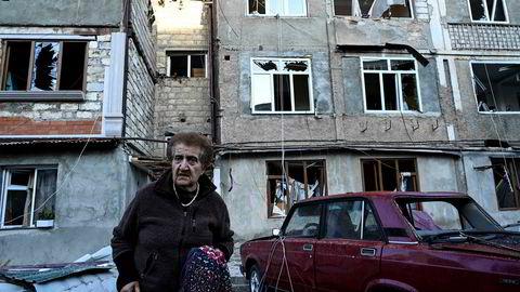En eldre kvinne bærer sine eiendeler vekk fra leilighetskomplekset som er hardt rammet av kampene i byen Stepanakert i Nagorno-Karabakh.